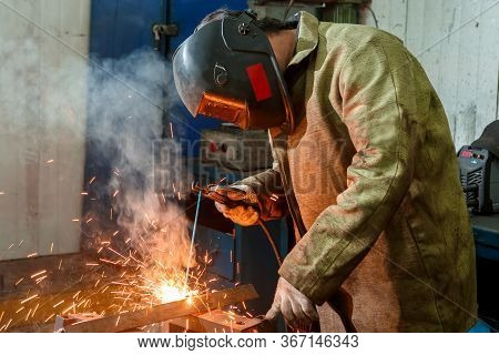 A Worker In A Welding Mask For Welding Metal Cooks A Metal Corner, A Lot Of Fire Sparks