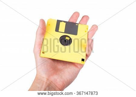 Single Bright Yellow Floppy Disk, Pastel Computer Diskette Being Held In Hand, Shown, Presented To T