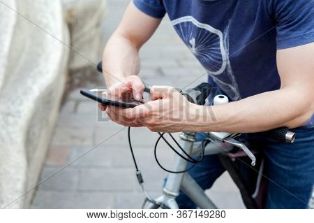 A Young Man Holding A Smartphone Sitting On A Bike Resting His Hands On The Handlebars. Biker / Cycl