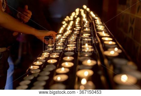 Lots Of Votive Candles Lit, A Hand Lighting A New Candle. Memory And Prayer Simple Spiritual Religio