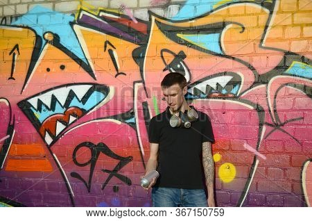 Young Caucasian Graffiti Artist In Black T-shirt With Silver Aerosol Spray Can Near Colorful Graffit