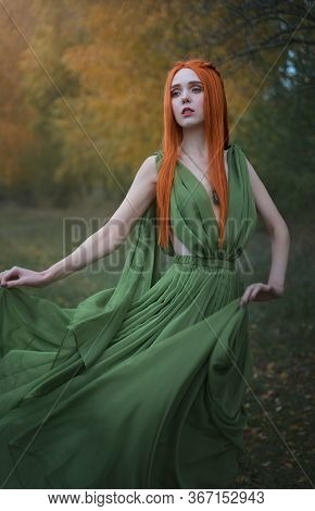 A Beautiful Long-haired Red-haired Elf Girl Stands In The Wind In The Autumn Forest. A Fairy Woman W