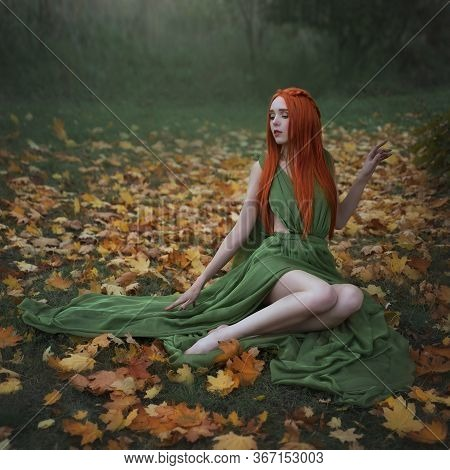 A Beautiful Long-haired Red-haired Elf Girl Is Sitting Under A Yellow Maple Tree In The Autumn Fores