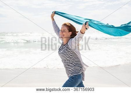 Happy smiling woman running with lightblue scarf enjoying at beach. Beautiful woman holding blue fabric at wind with copy space. Middle aged mature woman having fun, freedom and carefree concept.
