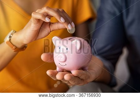 Close up of man holding pink piggybank while woman putting coin in it. Indian young couple saving money for their wedding. Close up of woman hand putting euro money in piggy bank to save.
