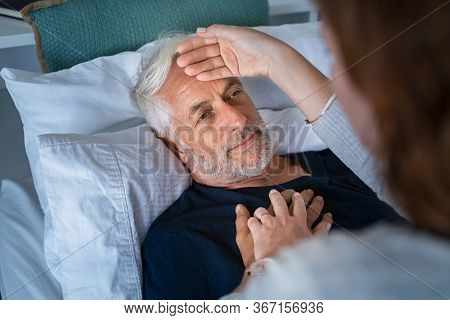 Woman checking fever temperature of senior man lying on bed. Mature husband resting at home feeling symptoms of the flu while wife checking fever by touching forehead. Close up face of old sick man.