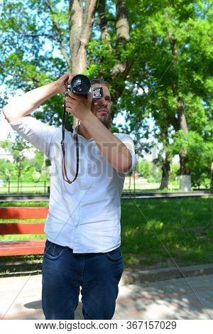 Photographer Holds Retro Camera With Big Lense.