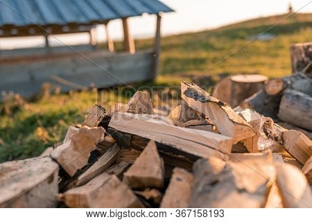 Pile Of Firewood Lying In Forest Countryside. Close Up Stacked Firewood Near Firewood Shed. Ready To
