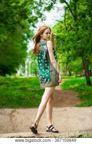 Full body portrait of a young beautiful red hair woman in green flowers dress, summer park outdoor