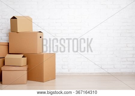 Moving Day Concept - Cardboard Boxes And Copy Space Over White Brick Wall Background