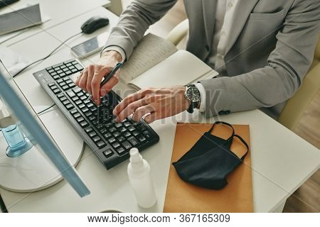 Close-up of unrecognizable businessman typing on computer keyboard while sitting at desk with facial mask and antiseptic bottle during quarantine