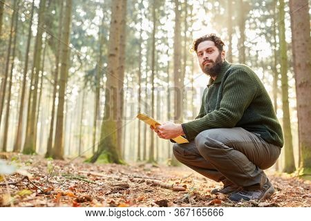 Young forester with checklist in forestry for sustainable forestry