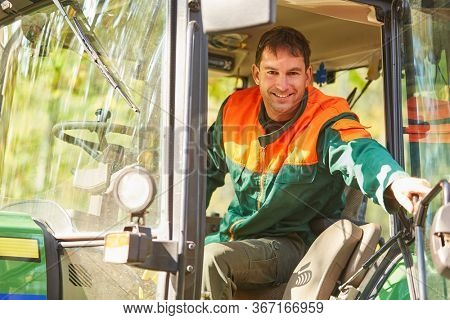 Smiling forest worker is sitting in the cabin of a forest tractor in the forest