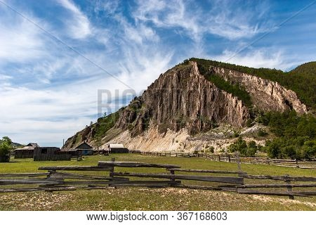 Old Village Under The Rocks. Decrepit Fence From The Boards. Clouds On The Blue Sky. Forest In The H