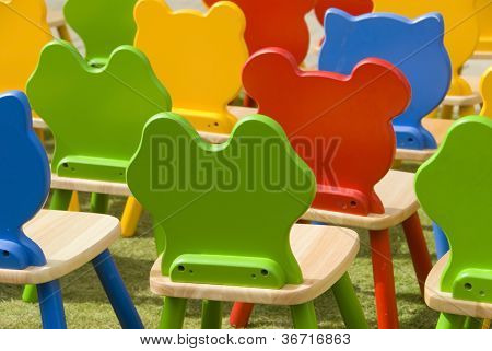 Colourful kids chairs in an outdoor playground poster