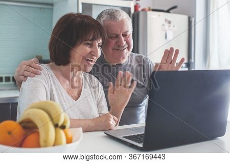Elderly couple looking at computer in the kitchen. Happy seniors with laptop at home Adult man and woman communicate online