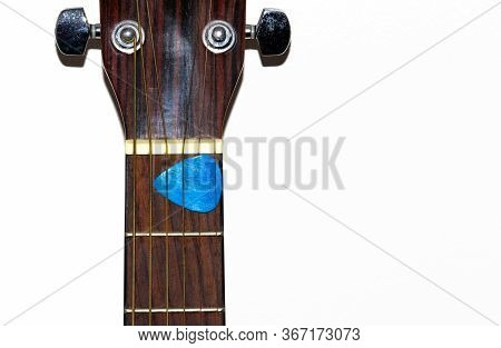 Isolated Guitar Fretboard With Plectrum Stuck Between The Strings.