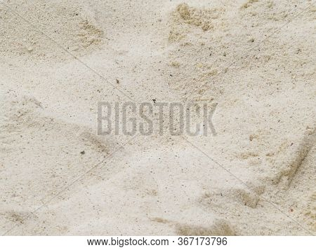 Sand On The The Beach As Background. A Close Up Shot Of An Uneven Dry Sand In A Sandy Beach. White S