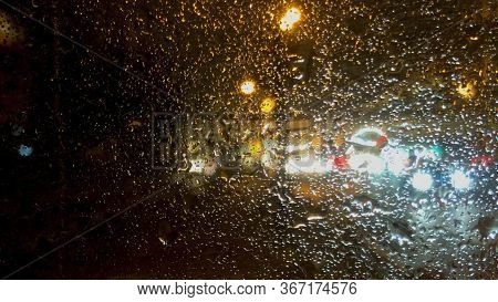 Abstract Background. Window Glass With Unfocused Raindrops. Unfocused City Traffic Through Glass Wit