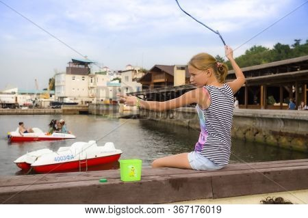 Anapa, Russia On August 12, 2015: Girl Catches Fish In The River. Teen With Fishing Rod Catching Fis