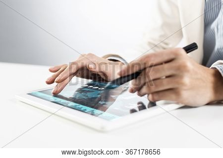 Broker In White Suit Using Tablet Computer For Financial Data Analysis. Close-up Of Male Hands Touch