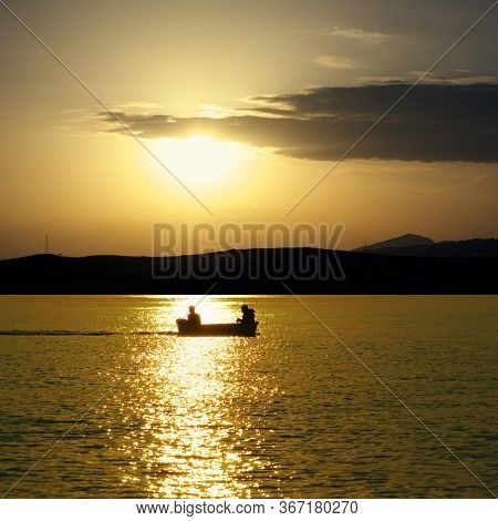 sea of Sicily at golden sunset, silhouette boat and two fishermen