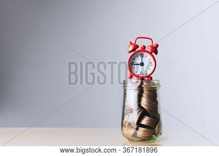 Red Alarm Clock And Coins In Glass Bottle. Time Counting Down For Retirement And Pension. 401k, Pass