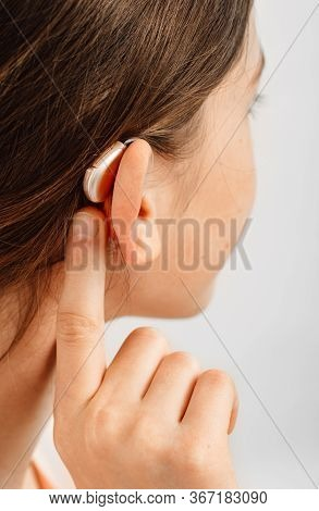 Hearing Solution For Children. Girl Pointing A Hearing Aid, Treatment Of Deafness In Children