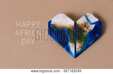origami heart, patterned with a map of Africa (furnished by NASA), and the text happy africa day on a brown background
