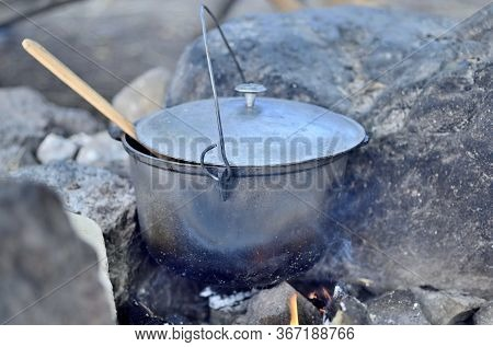 Cooking In A Cauldron On An Open Fire. Preparing Food At The Sta
