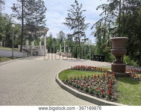 Old Alley In A Green Park. Flowerbed With Flowers. White Arbor. Vase Of Red Granite.
