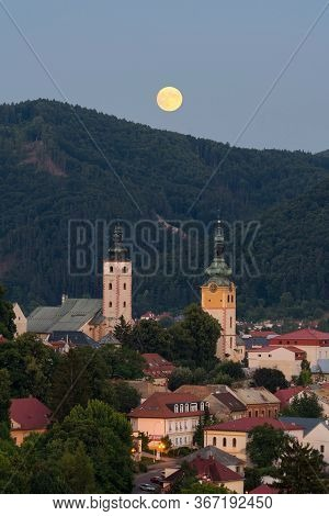 Supermoon Over Historical Centre Of Banska Bystrica. Middle-age Castle Barbican And Church In Centra
