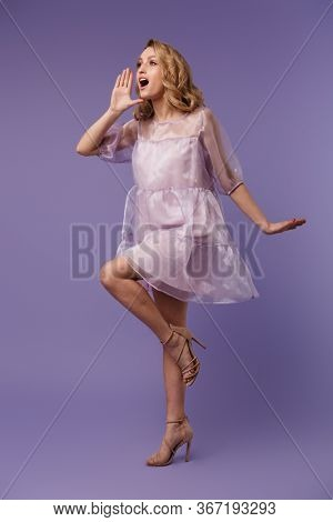 Full length photo of nice caucasian woman screaming and looking aside isolated over purple background