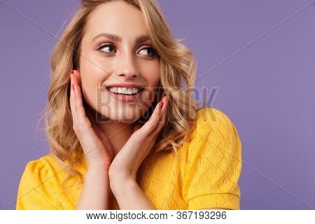 Image of nice cheerful woman smiling and looking aside isolated over purple background
