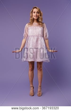 Full length photo of nice pleased woman posing and looking at camera isolated over purple background