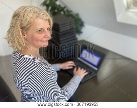 A Casually Dressed Caucasian Middle Aged Woman Is Installing A Laptop Computer With A Stack Of Sever