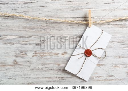 White Envelope Hanging On Rope On Wooden Background. Twine Rope With Wooden Clothespins. Letter Enve