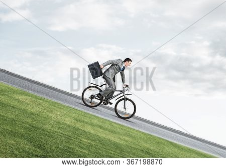 Young Man On Bicycle Fast Riding Downhill At Sunny Day. Businessman On Bike Hurry To Work. Corporate