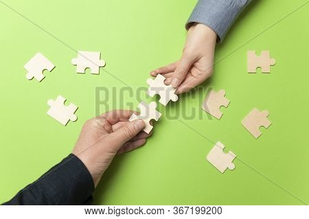 Two Hands Connect Puzzles On A Green Background. Cooperation And Teamwork In Business. Collaboration