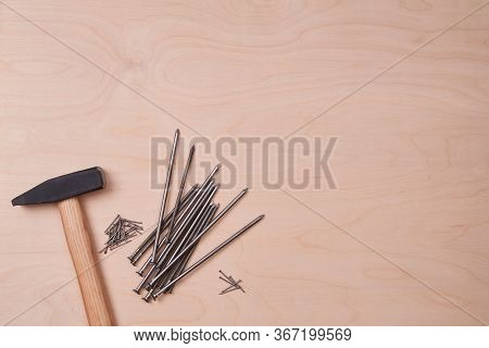 Hammer Equipment And Different Sizes Of Tacks. Building And Renovation Concept. Isolated On Wooden B
