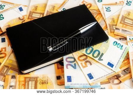 Black Roller Pen On A Black Checkered Notebook. Mani Euro Banknote On Background. Business Concept.