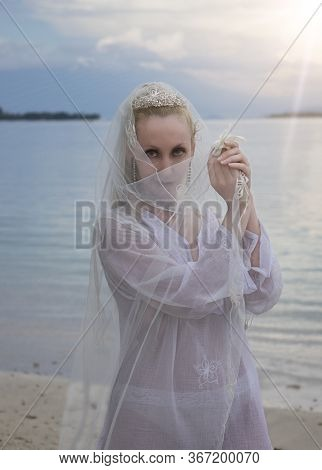 Woman In A Bride's Clothes Covers Her Face With A Veil, Stands In The Sea In The Early Morning.