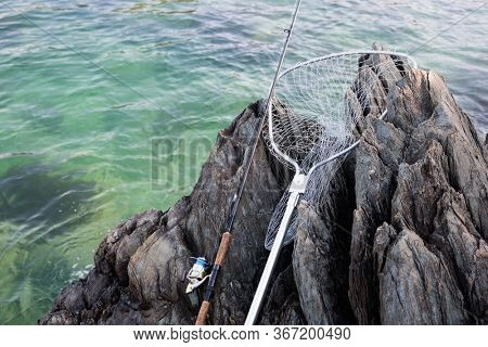 Spinning and landing net on a rocky shore by the sea