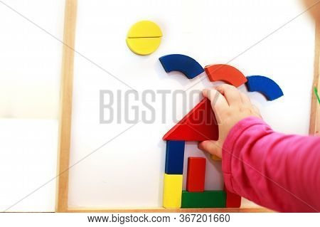 Child Plays Wooden Magnetic Educational Game. Girl Plays With A Toy On A White Background.