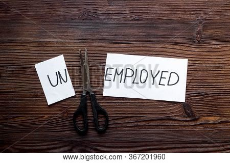 Employment, New Job Concept. Torn Paper Sheet - Unemployed - Sciccors On Wooden Table Top-down