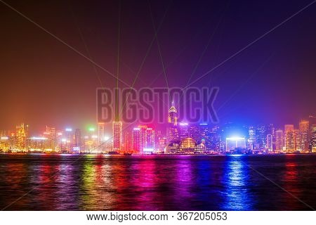 Hong Kong Island Skyline With Light Show Viewed From The Victoria Harbour Waterfront. Hong Kong Is A