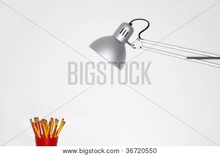 Angle poise lamp and pencil holder with white background