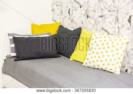 Six Bright Pillows On The Sofa In The Bedroom. Gray Striped Pillow, Yellow Pillows, Black Pillow To