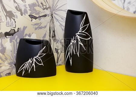 Two Black Vases On A Yellow Shelf In A Bedroom. On Vases A Florid Pattern. Vases Stand In A Corner,