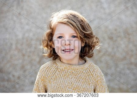 Happy blond child with long hair outside looking at camera